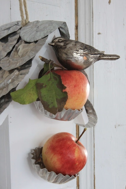 fall Nordic decor with apples on metal holders, a fake bird and a fake bird house