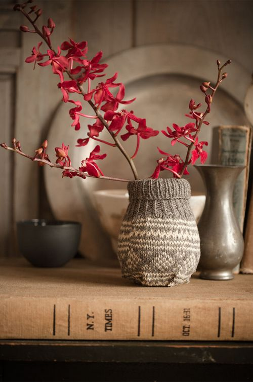 a vase wrapped with a knit piece and branches with burgundy blooms on it looks laconic and cozy