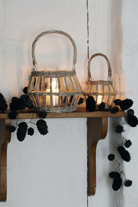 candle lanterns placed in baskets and pinecone garlands on the shelf for a natural fall feel