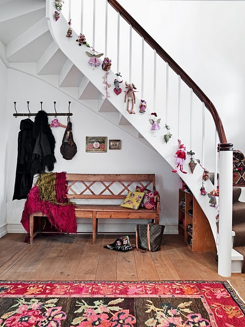 Kids toys is a great alternative to ornaments to hang not only on a Christmas tree but on a staircase too.