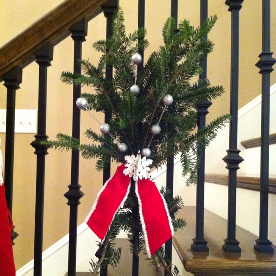christmas stairs decoration ideas instead of swags of greenery trailing down the banister try these evergreen bunches use