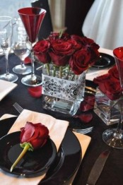 a bold red and black Halloween tablescape with plenty of red roses, burgundy goblets and some black plates is a very chic idea