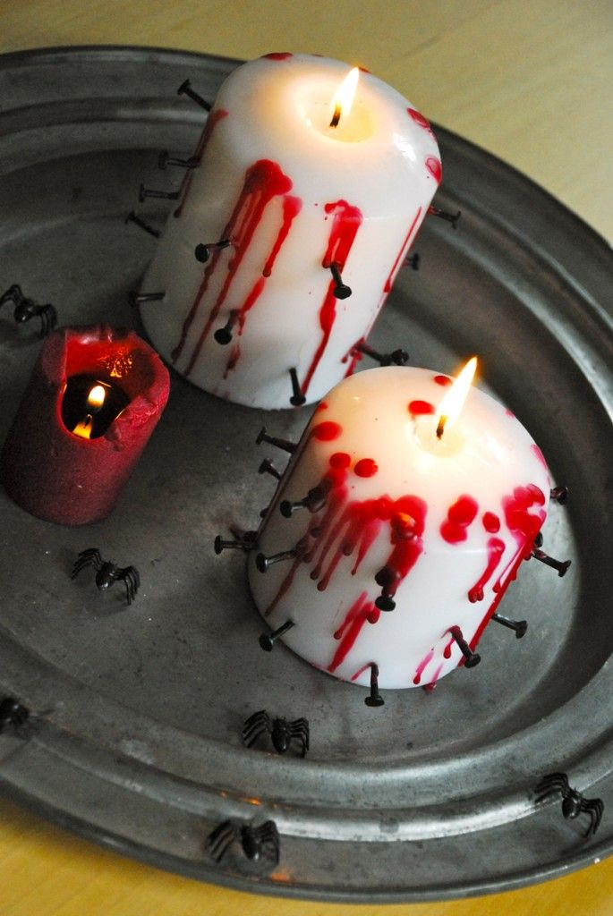 basic pillar candles decorated with black nails and red wax look bold and very Halloween appropriate
