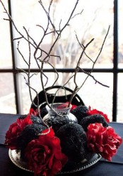 a refined red and black Halloween centerpiece of bold blooms and black glitter skulls plus branches in a vase in the center