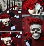 refined red and black Halloween styling with a red tablecloth, roses, black candles and skulls is edgy
