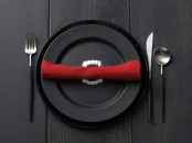 simple styling with black plates, black cutlery and a red napkin with vampire teeth for a modern Halloween party