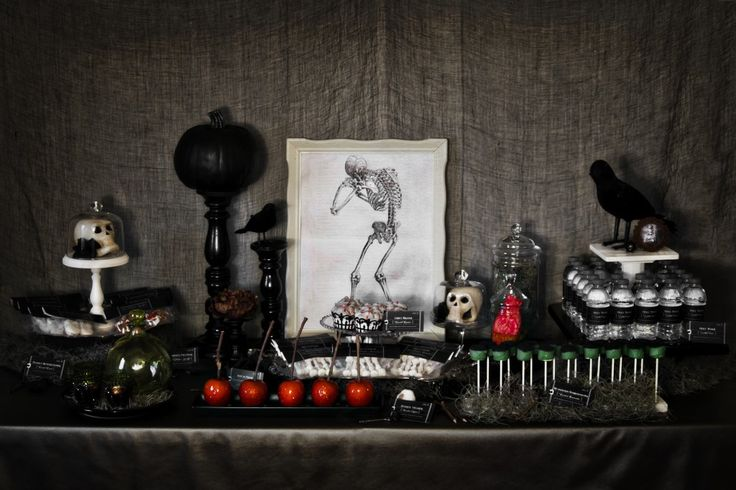 a vintage Halloween dessert table with candied apples, various desserts, a black pumpkin on a stand and a crow is chic and stylish