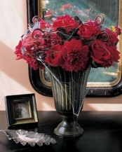 an easy Halloween arrangement of red roses and lotus swirls plus spiderwebs can become a centerpiece, too