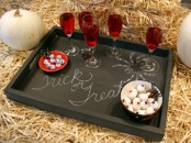 a black chalkboard tray with red drinks, candies and chalking for a rustic Halloween party