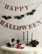 bats and bloody letters banners, dark fruit and burgundy goblets for styling your table for Halloween