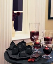 a black favor table with black paper bags and goblets with burgundy wine and candles floating in them look refined