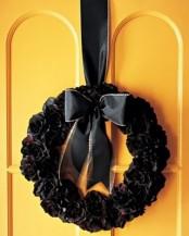 a black fabric flower wreath with a black ribbon bow is a stylish and elegant Halloween decor idea