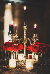 red roses pair up beautifully with deep purple and black candles in a gold candelabra for a Halloween decoration