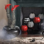black, white and red patterned pumpkins and matching witches' legs in a cauldron are amazing for Halloween decor