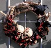 a dark Halloween wreath with black bloody roses, bones, skulls and spiderwebs