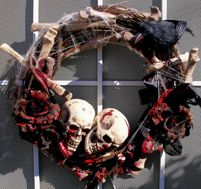 a dark Halloween wreath with black bloody roses, bones, skulls and spiderwebs