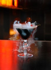 a black Halloween cocktail with smoke, a red cherry and a black spider is perfect for a Halloween party