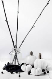 black and white minimalist Halloween decor with white pumpkins, black branches in a jar, some black beads is a lovely idea to rock