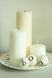 white pillar candles and white balls with letters compose a cool Halloween decoration in minimalist style