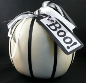 a white pumpkin with black and white ribbons and a black and white tag is a cool minimalist Halloween decoration to rock