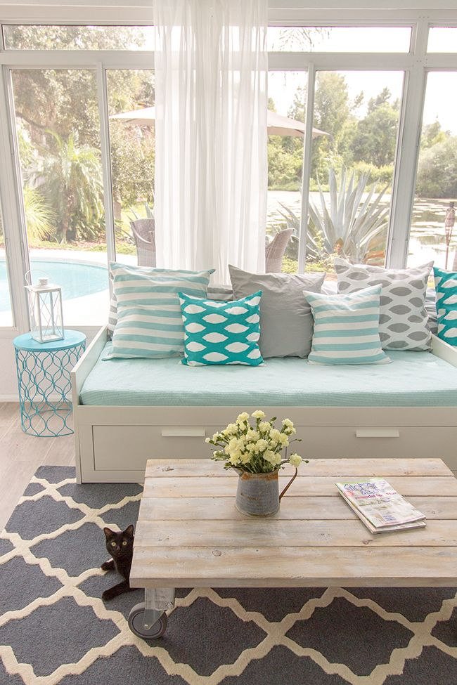 a beach farmhouse sunroom with neutral furniture with storage, a wooden table and light blue and mint blue pillows and upholstery