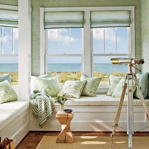 a coastal sunroom with a built in L shaped bench with storage, light green walls, curtains and pillows