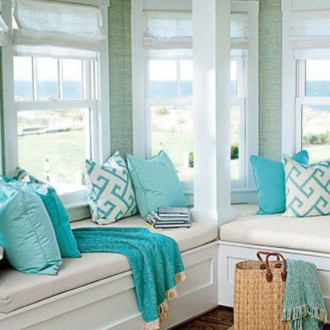 a beach sunroom with built-in benches, tiffany blue and printed pillows plus a cool coastal view
