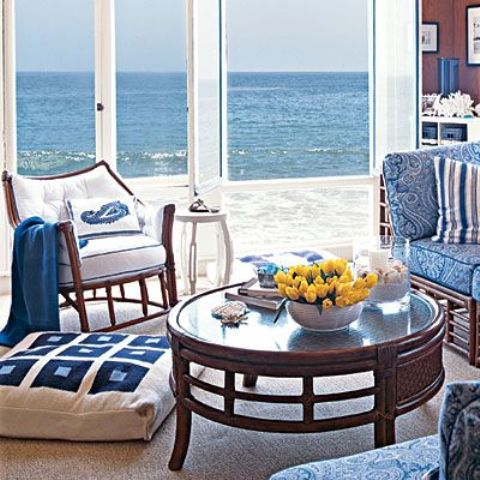 a vintage beach sunroom with dark and blue and white upholstery furniture, a dark table and a marvellous view