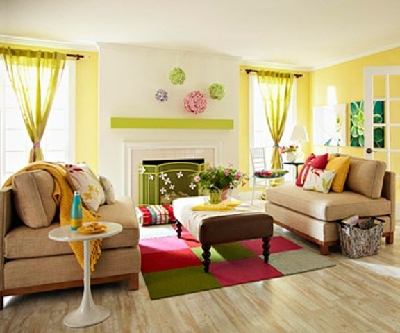 a bright and colorful spring living room with yellow accent walls and curtains, with a colorful square rug, bright pillows and blankets and a green fireplace screen