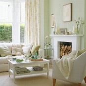 a serene spring living room with light green walls, a fireplace, artworks, blooms, floral textiles and green touches is very light and welcoming