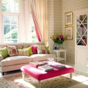 a bright and fun spring living room with printed wallpaper, colorful and floral pillows and curtains and a bold pink ottoman