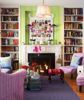 a bright spring living room with green walls, lilac chairs, printed pillows and stools and bold blooms