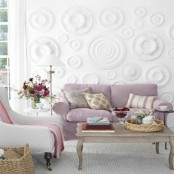 an airy living room with a decorative textural wall, a lilac sofa, a wooden table, some pink and lilac pillows and bold blooms