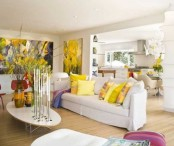 a bright spring living room with bold floral artworks, yellow printed pillows, oversized blooms in vases and pink pillows