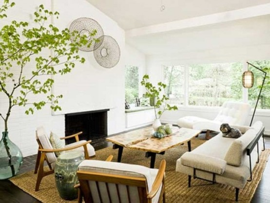 an airy and serene modern living room with neutral furniture, lamps, decorative plates and lots of greenery