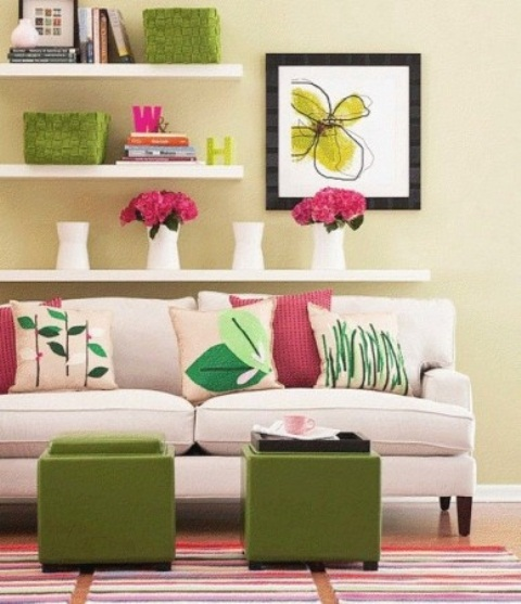 a bright and cool living room with pale yellow walls, open shelves, bright artworks and accessories, embroidered pillows and green ottomans
