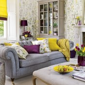 a bright spring living room with floral walls, a grey sofa, yellow and purple accessories, linens and lamps
