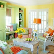 a cheerful living room with yellow walls, a green storage unit with pillows, orange touches and bold blooms