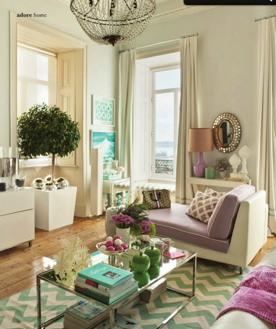 a refined living room in neutrals accented with green and purple touches, a crystal chandelier, a mirror and chevron patterns