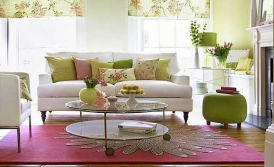 a bright and fun living room with floral and green textiles, a pink floral rug, a green ottoman and greenery and blooms