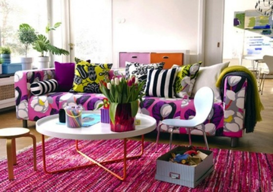 a bright spring living room with a floral print sofa, printed pillows, a pink rug and bold blooms and greenery
