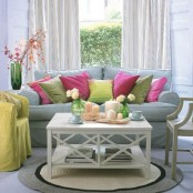 a pastel spring living room with a blue sofa and colorful and bright pillows, a yellow chair and bright blooms and candles