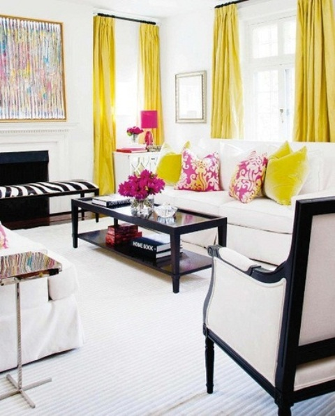 a monochromatic living room with bold yellow curtains, yellow and pink pillows, a pink lamp and blooms