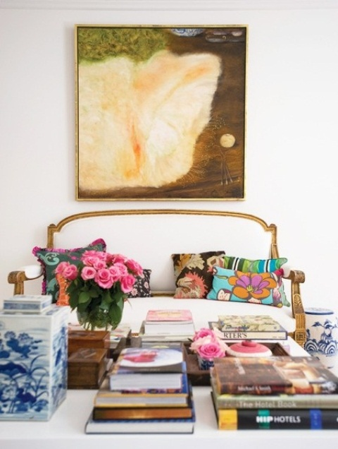 a bright and fun living room with a statement artwork, a refined sofa with colorful pillows, blooms and books is whimsical