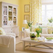 a colorful spring living room with yellow walls, neutral furniture, green and yellow pillows and blankets, yellow floral curtains, bright blooms and greenery