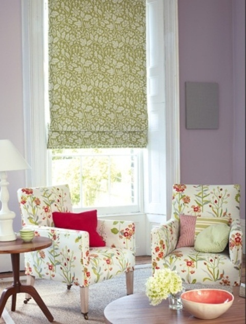 an elegant and cheerful spring living room with lilac walls, floral chairs, a floral curtain, a white lamp and some bright touches