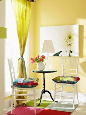 a bold living room with yellow walls, a yellow curtain, colorful pillows and artworks and a bright rug