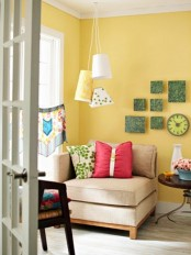 a bright living room with yellow walls, colorful pillows, pendant lamps, bold artworks and printed and bright textiles