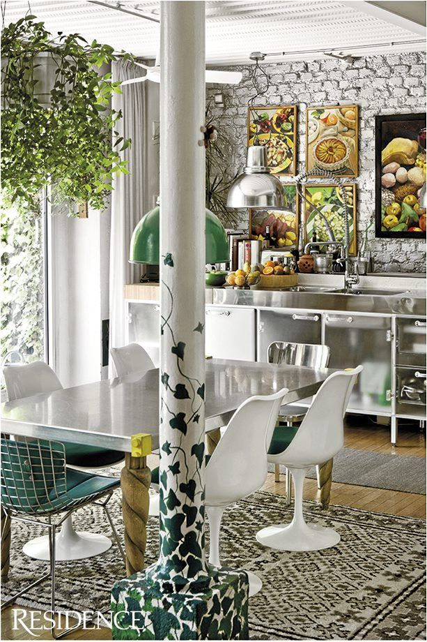 colorful artworks, a unique pillar, dark green chairs and printed rugs for a catchy look
