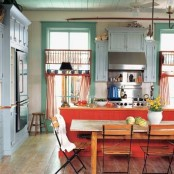 a bold vintage kitchen with green walls, a red kitchen island, a powder blue cabinet, stainless steel appliances and orange chairs